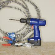 Cordless drill next to wire cutters and cable - stock photo
