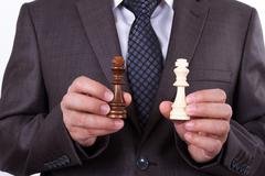 Stock Photo of businessman showing chess piece kings