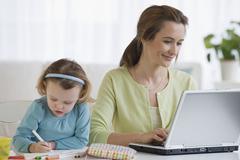 Äiti työskentelee vieressä tytär väritys Kuvituskuvat