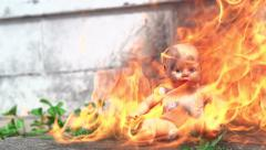 Small baby doll sitting in flame Stock Footage