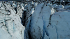 Aerial view of moraine covered deep crevasses Knik Glacier  Alaska, USA Stock Footage
