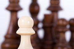 Stock Photo of pawn against chess pieces on board