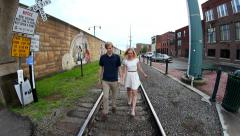 Young couple walking on rail road tracks then hugging Stock Footage