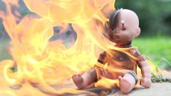 Baby doll with gasoline burning Stock Footage