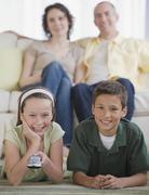 Perhe kaksi lasta katsomassa televisiota Kuvituskuvat