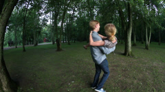 Young man holding and spinning beautiful blonde woman. Stock Footage