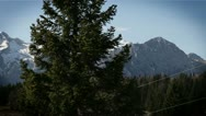 Stock Video Footage of Panoramic shot of mountains from the chairlift,  passing a spruce