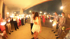 Newly married couple walking through gauntlet of sparklers Stock Footage