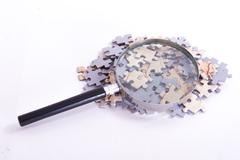 Stock Photo of magnifying glass on puzzle pieces