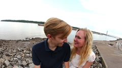 Pull away shot of couple with barge on river behind them Stock Footage