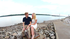 Young couple sitting by Mississippi River - stock footage