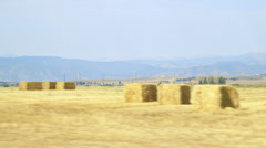 Driving on a rural road next to hay field Stock Footage