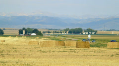 Traffic on a farm road and distant Colorado mountains Stock Footage