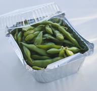 Close up of edamame in takeout container - stock photo