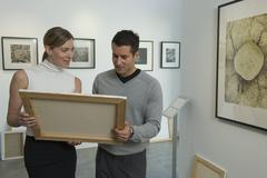 Curators examining painting in art gallery - stock photo