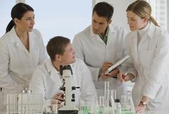 Scientists working together in pharmaceutical laboratory Stock Photos