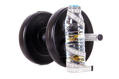 Dumbbell and water with tape measure Stock Photos