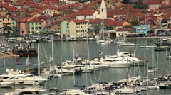 Isola s port with a lot of sailing boats and the town in behind Stock Footage