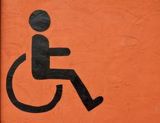 the symbol handicapped on orange wall background - stock photo