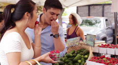 Young Couple Tasting Fresh Strawberries at Farmers Market Stock Footage