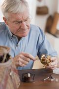 Senior man fixing fishing reel Stock Photos