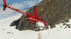 Helicopter taking off snow covered wilderness, Alaska, USA Stock Footage