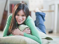 Stock Photo of Mid-adult woman lying on floor hugging blanket
