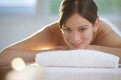 Stock Photo of Mid-adult woman lying on massage table with candle in foreground