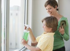 Mother and son washing windows - stock photo