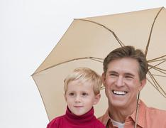Father and child under umbrella Stock Photos