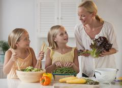 Mother and daughters in the kitchen - stock photo