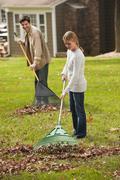 Man and girl raking leaves Stock Photos
