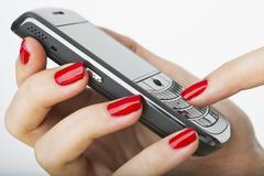 Nainen yllään punainen kynsilakka kutoma matkapuhelin Kuvituskuvat