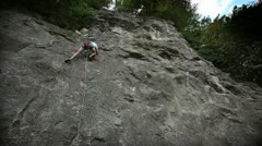 Man rock climbing shot from below Stock Footage