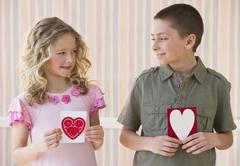 Young children holding Valentine cards - stock photo