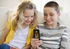 Sisarukset katsot kännykkä Kuvituskuvat