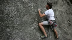 Young man rock climbing on a big natural rock - stock footage
