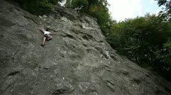 Man rock climbing in beautiful nature shot from below - stock footage