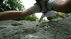 Young man rock climbing in nature shot from below Stock Footage