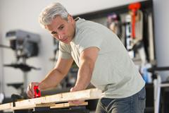 Handyman measuring a piece of wood in workshop Stock Photos