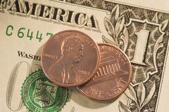 Pennies on top of American dollar bill Stock Photos