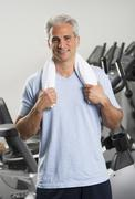 Man at the gym standing with towel around his neck - stock photo