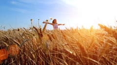 Little girl with arms outstretched in a wheat field - stock footage
