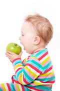 Baby eating green apple. Stock Photos