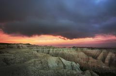 Stock Photo of USA, South Dakota, Thick gray clouds over mountains in Badlands National Park at