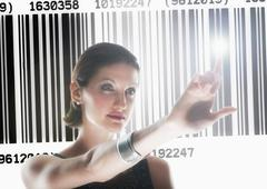 Stock Photo of Young woman standing by barcode