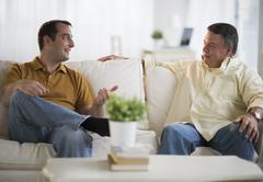 USA, New Jersey, Jersey City, Father and son talking on sofa in living room - stock photo