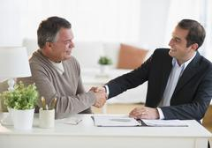 USA, New Jersey, Jersey City, Man shaking hands with financial advisor in home Stock Photos