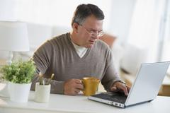 USA, New Jersey, Jersey City, Man using laptop, holding drink in living room - stock photo