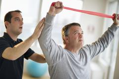 USA, New Jersey, Jersey City, Fitness instructor assisting man in gym - stock photo
